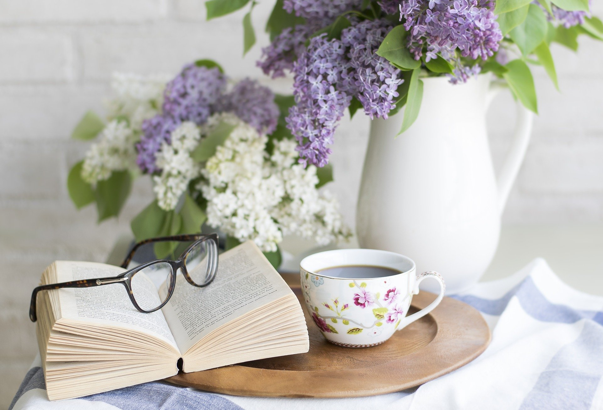 Tea with flowers, book and reading glasses
